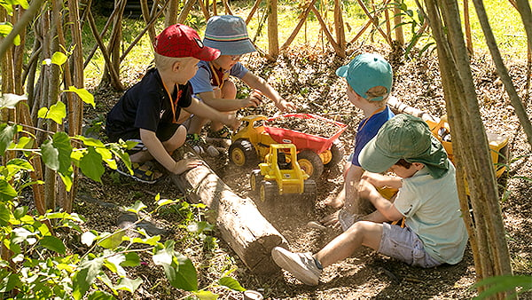 Boys playing with diggers in all weather outdoor play area