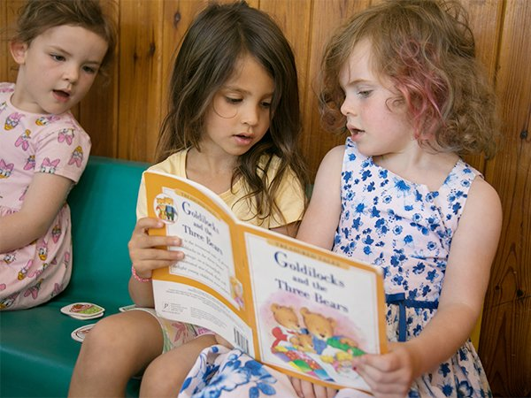 Girls reading a book indoors