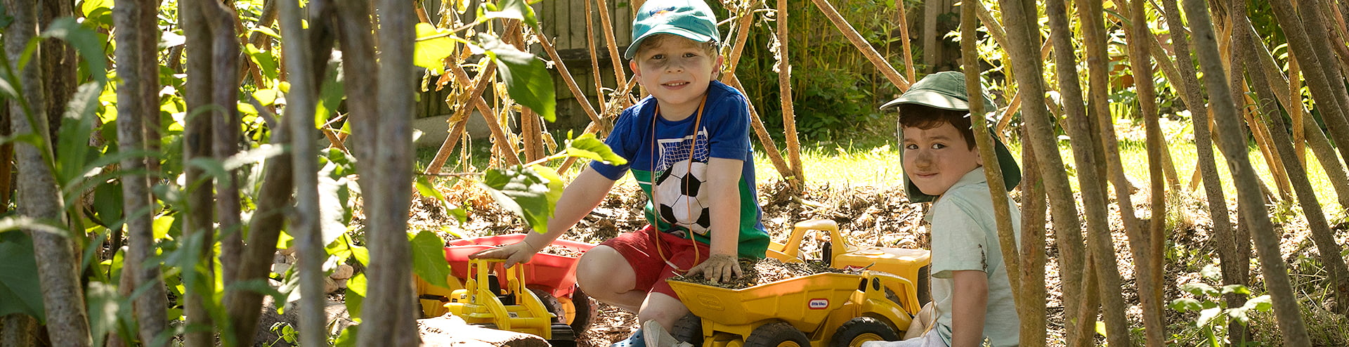 Two boys playing with diggers in Jigsaw garden