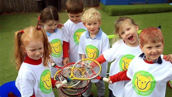 Children holding tennis rackets at Teddy Tennis