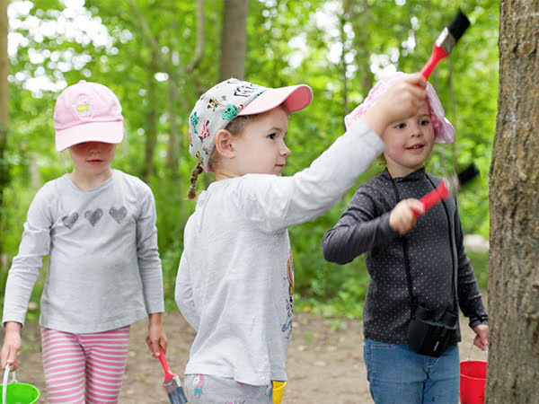Children brushing a tree in a wood