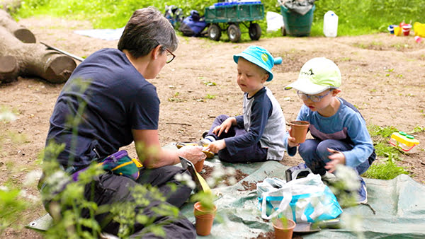 Two boys and a teacher sitting down at Woodland Explorers